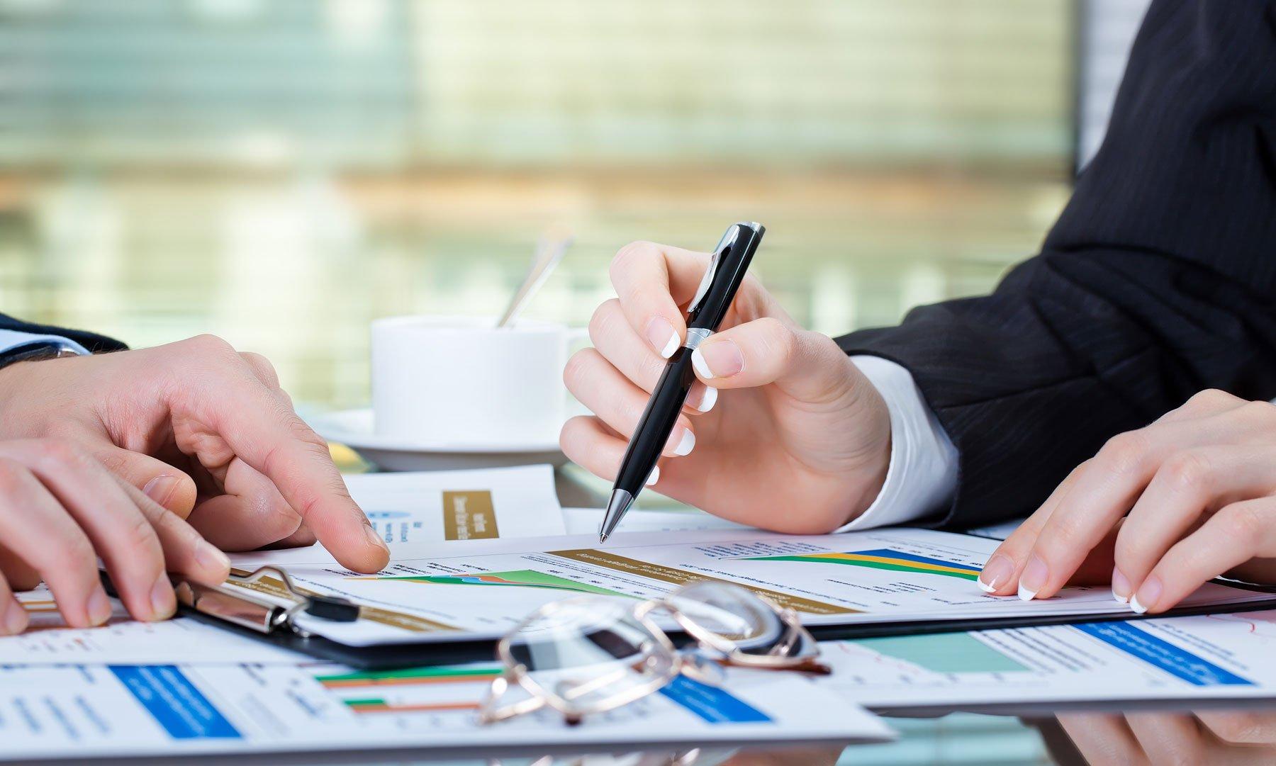 una mano che indica con una penna un foglio con dei grafici e di fronte un' altra persona che indica con il dito lo stesso foglio