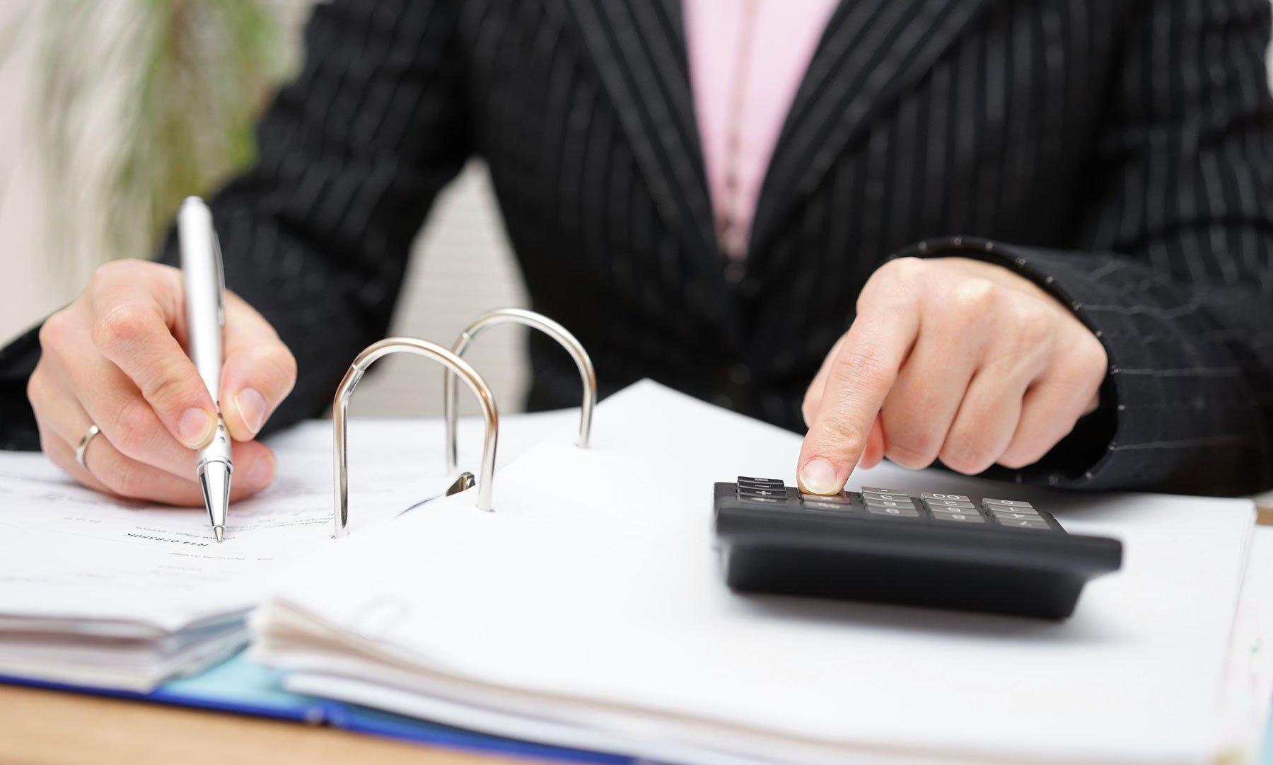una donna alla scrivania con una penna in mano che scrive in un foglio dentro a un raccoglitore e con l'altra mano sta usando una calcolatrice