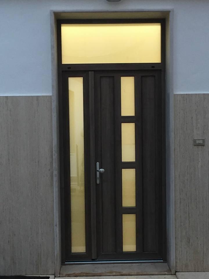 Porta chiusa di colore marrone scuro, costruita con legno e vetri