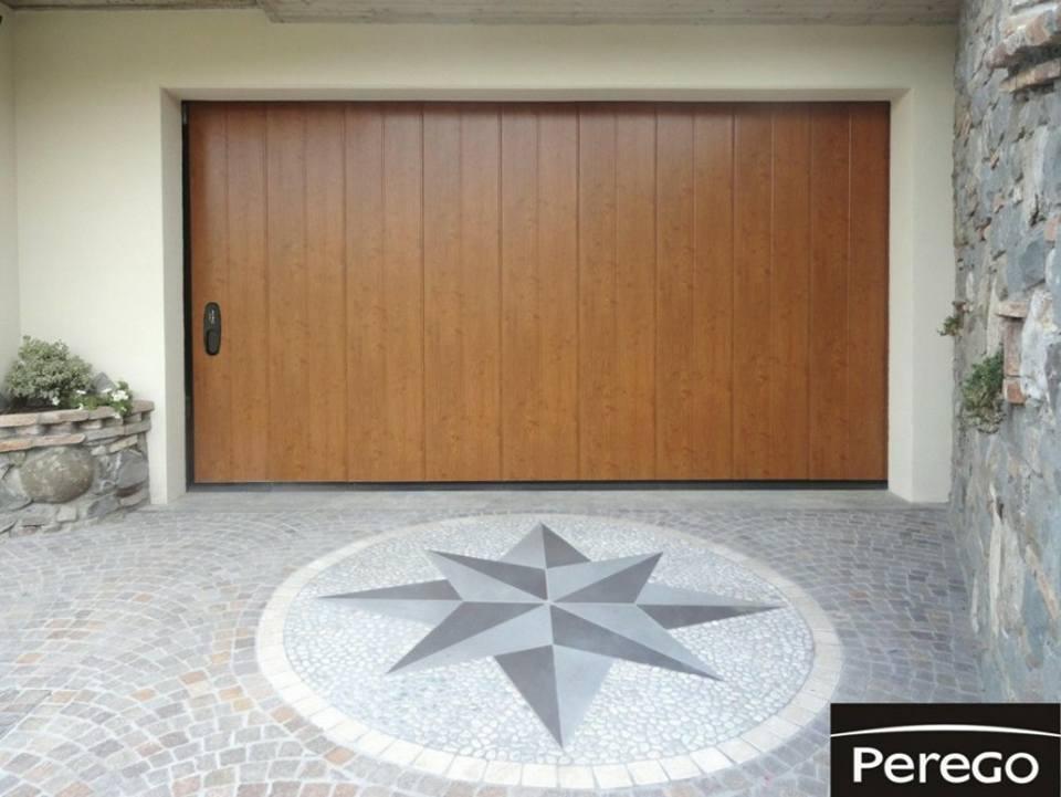 Porta chiusa ed in legno di un garage, con stella polare sul pavimento