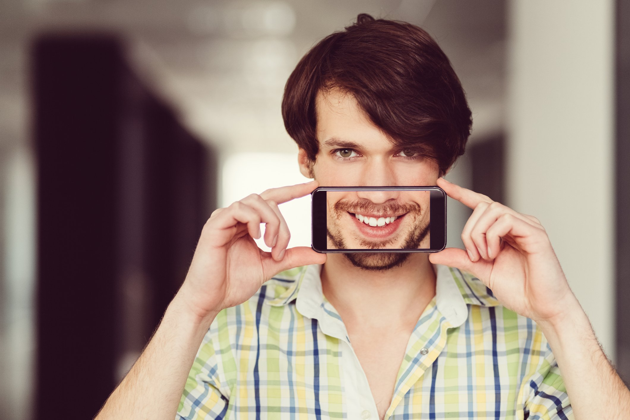 Man Holding iPhone in Front of Mouth