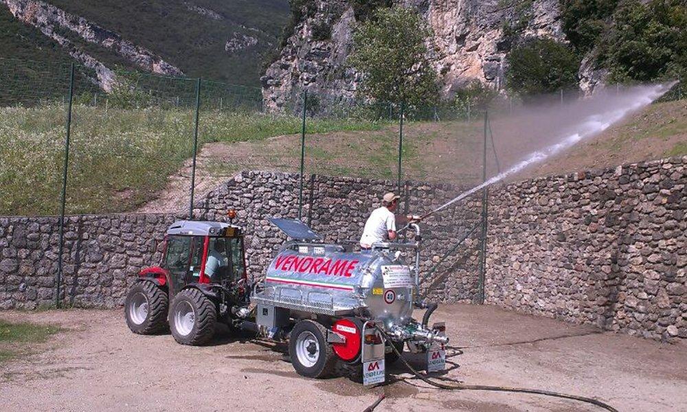 un uomo che spruzza dell'acqua con un idrante
