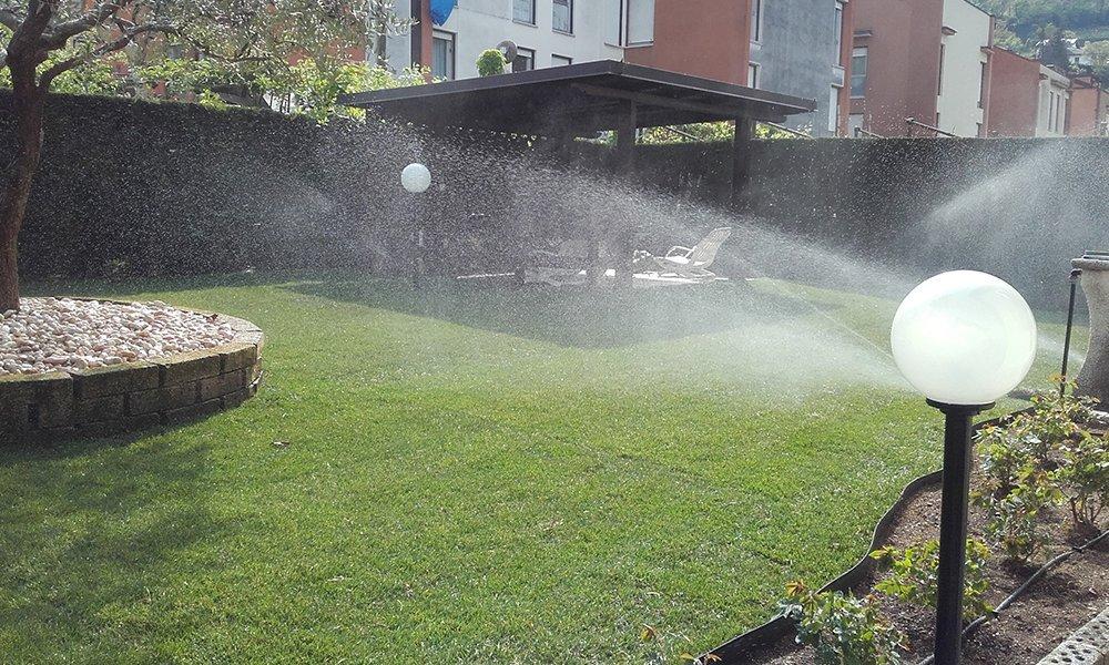 degli irrigatori che spruzzano acqua in un giardino con un gazebo