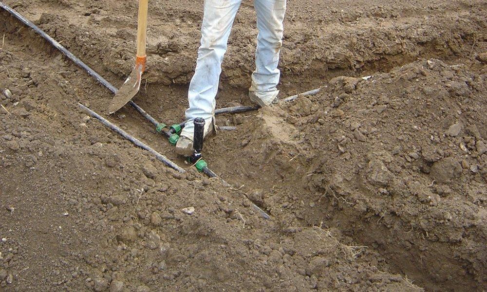 le gambe di una persona, una pala in un terreno e dei tubi di un impianto di irrigazione
