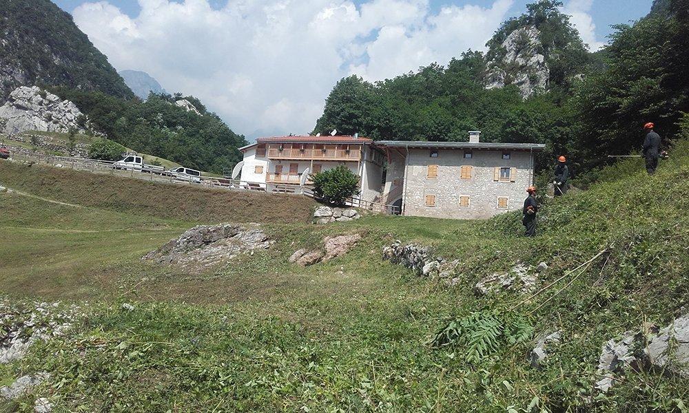 Delle case in montagna viste da lontano e dei giardinieri al lavoro