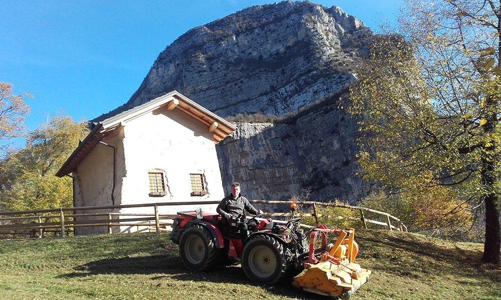 Un uomo su un mezzo agricolo è accanto una casa e una montagna