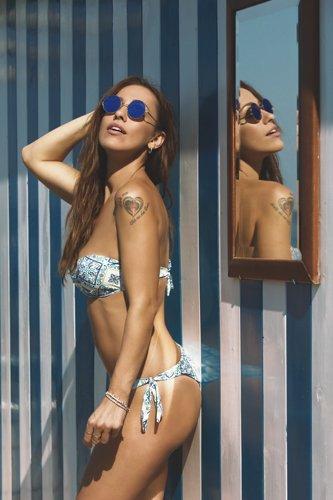 modella in posa con costume da bagno e occhiali da sole