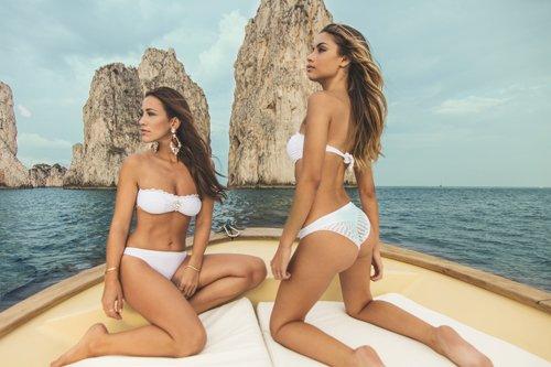 modelle su una barca con costume due pezzi