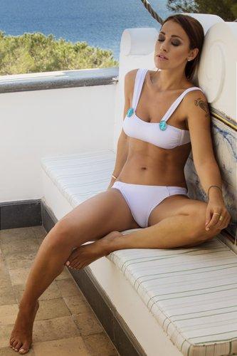 modella seduta con un costume bianco