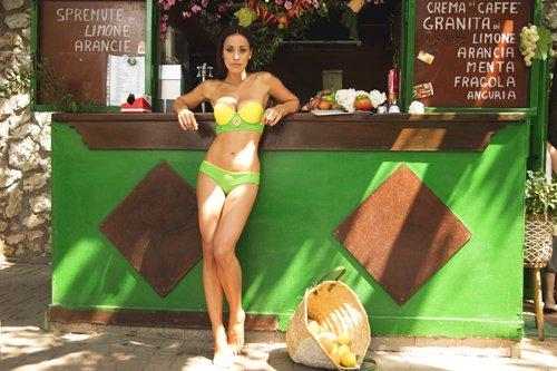 modella in posa davanti al bancone di un bar con cesto di frutta ribaltato