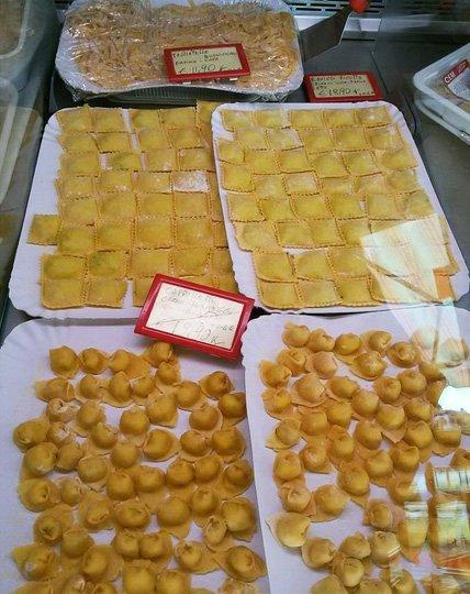 Dei vassoi con pasta all'uovo ripiena fresca in vari formati
