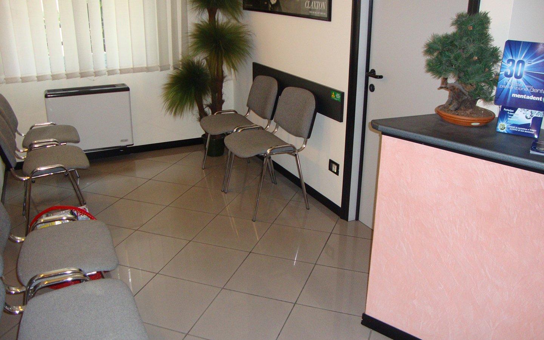 saletta d'attesa con delle sedie grigie, un vaso con una pianta e sulla destra il bancone della reception, un portaombrelli e un dispenser d'acqua