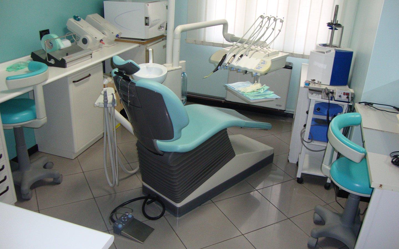 interno dello studio dentistico con un lettino azzurro, una sedia sulla destra, piano da lavoro e attrezzatura