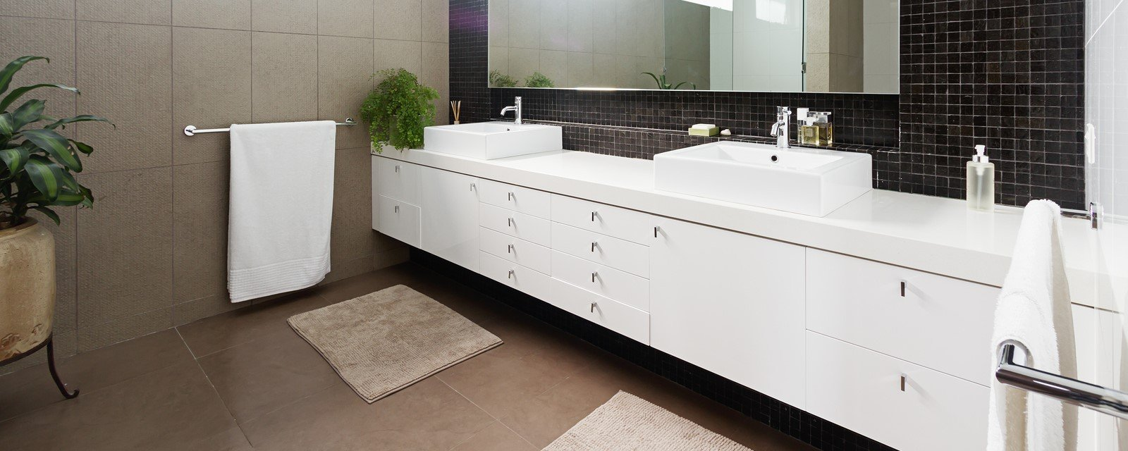 Pure white vanity on a black tile background.