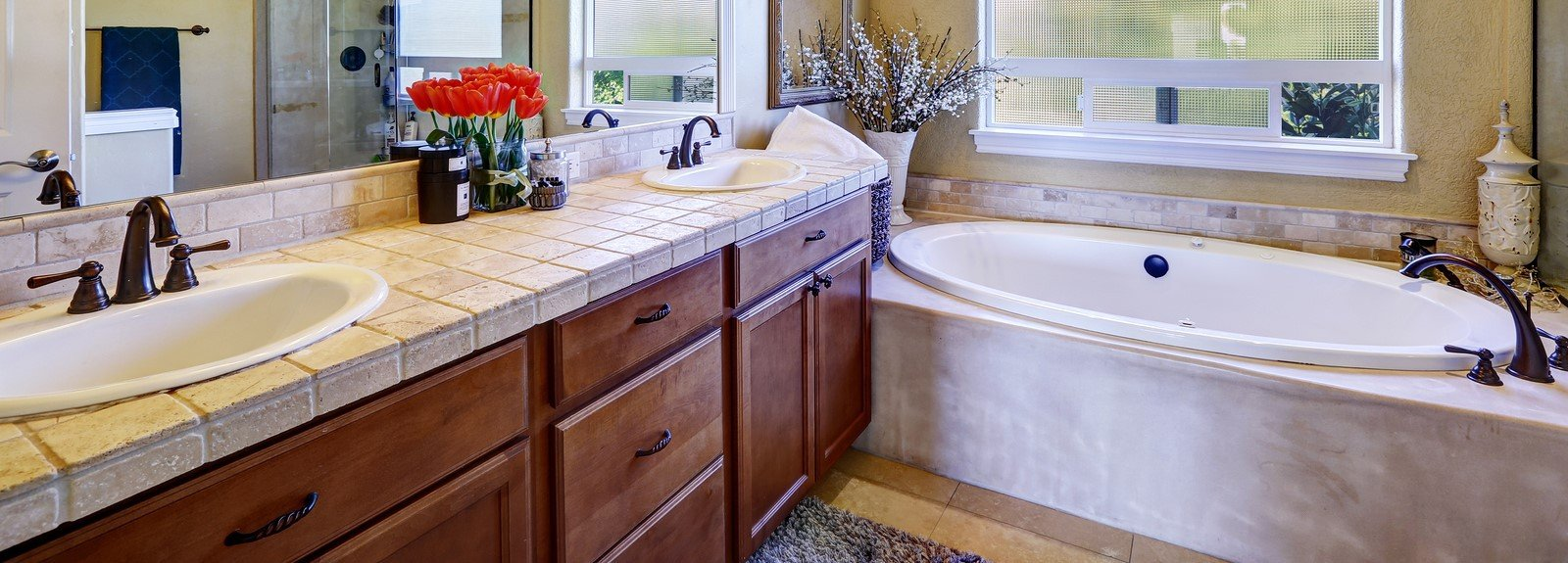 Traditional wood and tile vanity framed by an oval bath.