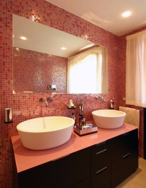 Parete di bagno di piccole piastrelle rosse e rose,mobile di legno con due lavandini
