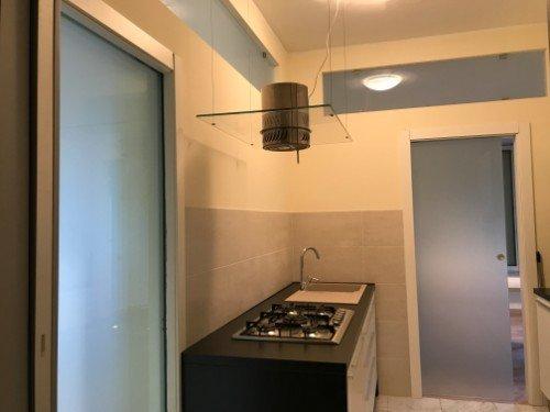 Cucina con porte scorrevoli di vetro e originale estrattore sulla cucina
