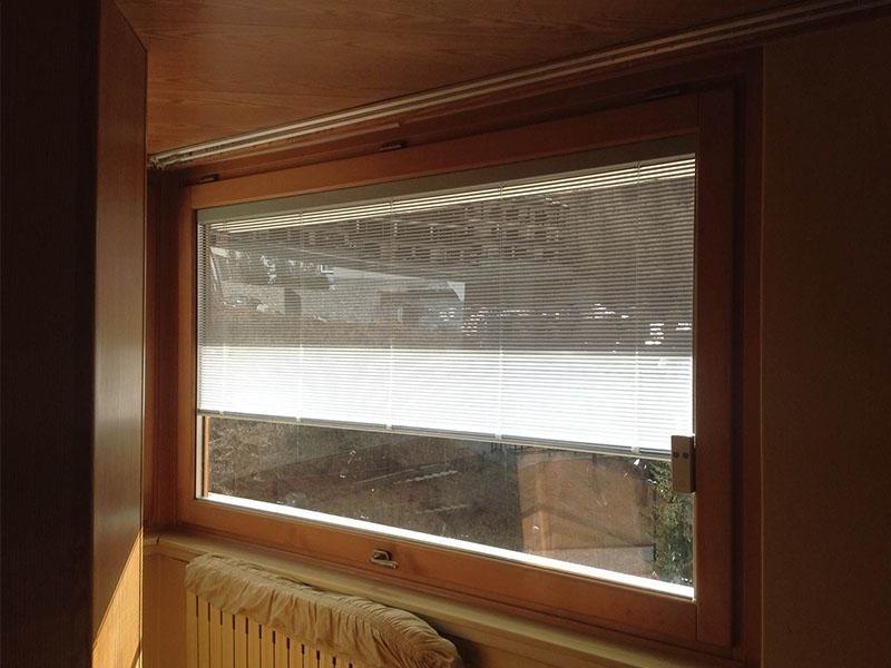 serramento in legno Pino Lamellare tinto Rovere Miele con veneziana interno camera elettrica. ( condominio Cervinia)