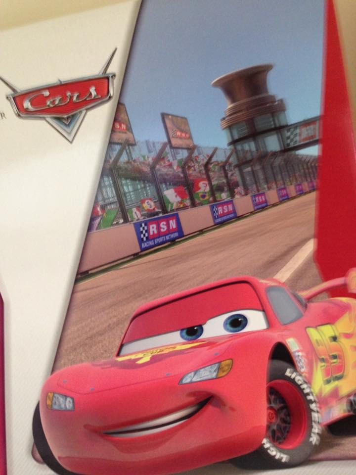un' immagine di una macchinina rossa tratta dal cartone animato Cars in un circuito
