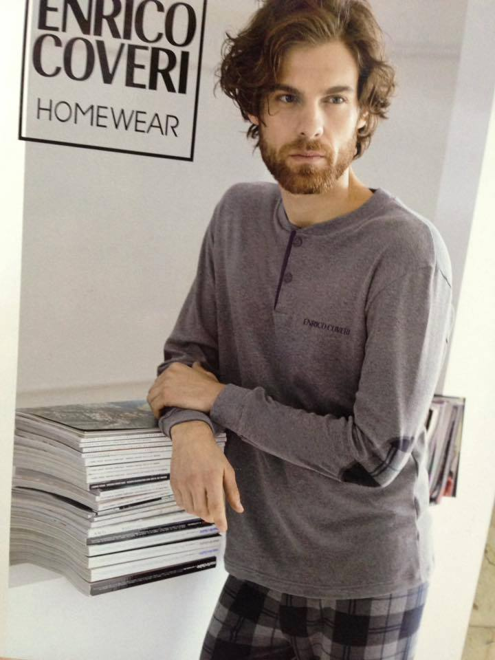 un uomo che indossa una maglia grigia a maniche lunghe e dei pantaloncini a scacchi bianchi e neri, marca Enrico Coveri