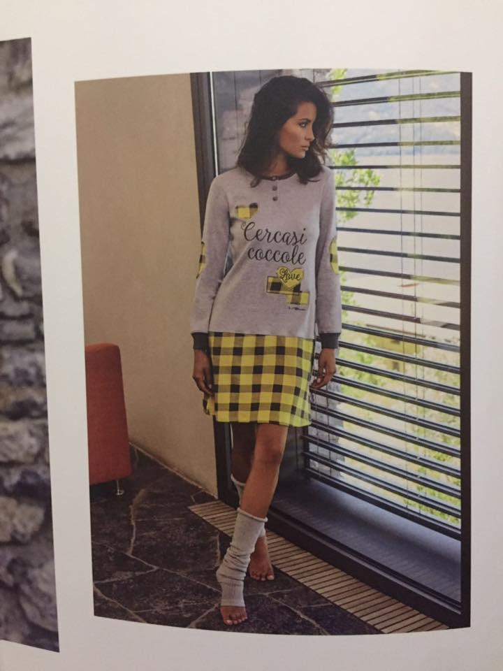 una donna vicino a una finestra che indossa una maglia grigia con scritto Cercasi Coccole e una mini gonna stile scozzese gialla e nera