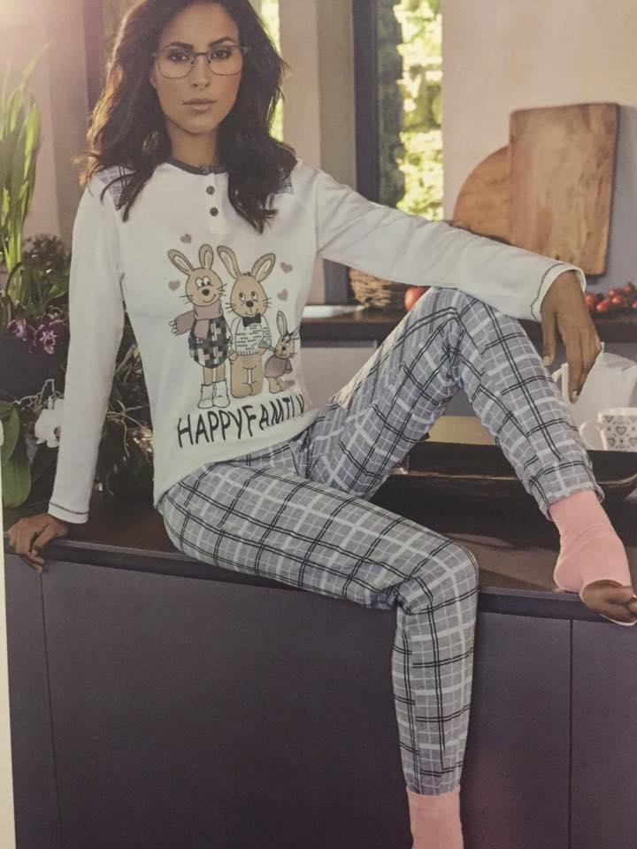 una donna seduta su una scrivania indossa una maglia bianca con disegnati dei coniglietti marroni e  dei pantaloni grigi a righe bianche e nere