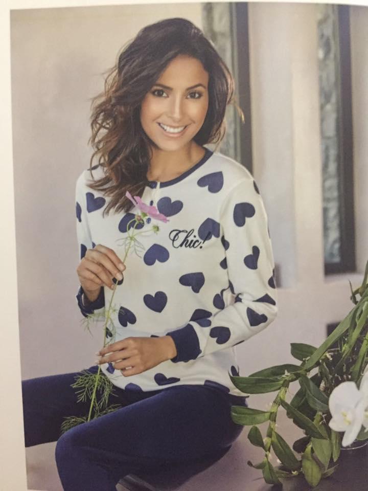una donna con un fiore in mano che indossa una maglia bianca con cuori viola e dei pantaloni blu