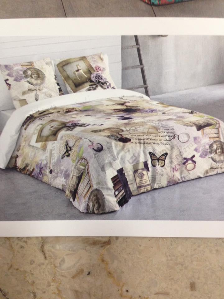 un letto con piumone e cuscini di color beige con disegni di cornici, farfalle e libri