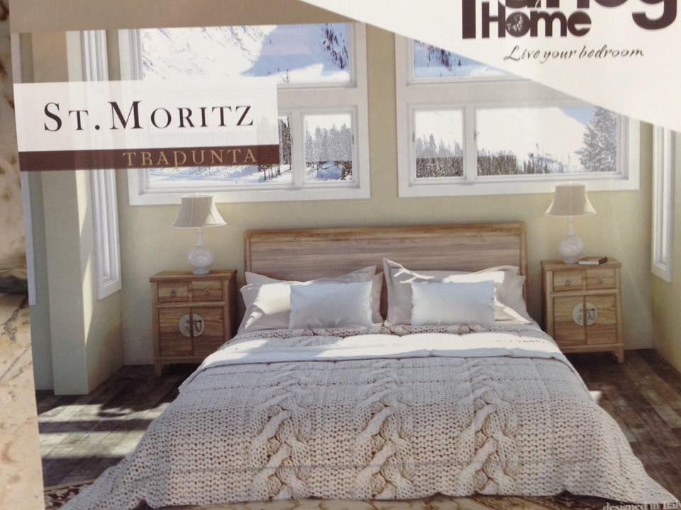 una camera da letto con comodiini in legno con sopra due lampade e un letto con cuscini e trapunta di color bianco