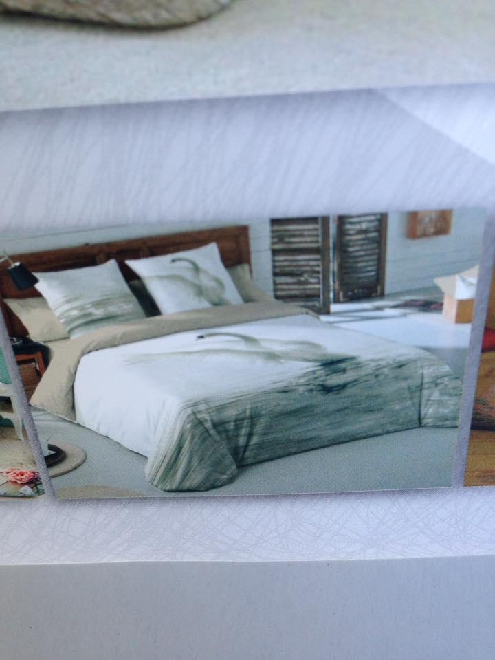 un letto con piumone e cuscini di color panna e beige e dei disegni grigi
