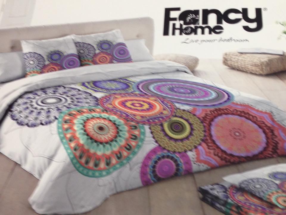 un letto con cuscini e piumone bianco con disegni verdi,rossi,blu,viola e gialli