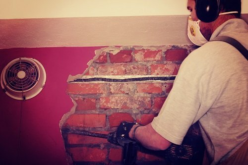 Operaio restaura muro in pietra