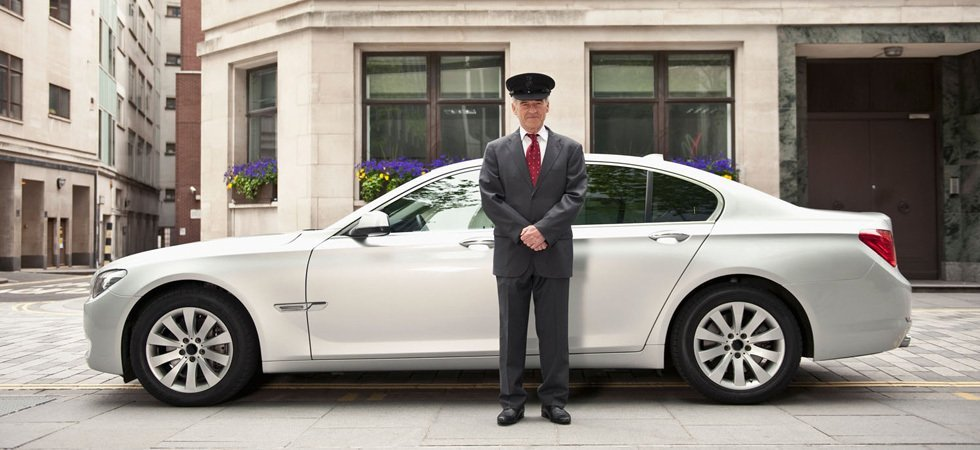 A uniformed chauffeur in front of a saloon