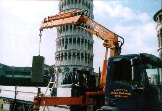 Autogru solleva una cabina, in sfondo la torre di Pisa