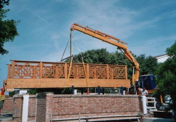 Gru che solleva una struttura in legno e mattoni