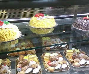 bancone con torte alla creama sopra e paste sotto