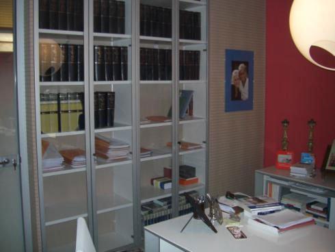 un armadio vetrina con dentro dei libri , una foto appesa alla parete e una scrivania bianca con sopra degli oggetti