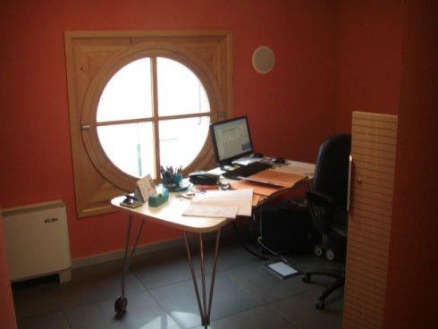 un ufficio con pareti arancioni, una finestra a oblò con rifiniture in legno, sulla sinistra un termosifone e in centro una scrivania bianca con sopra un computer e una sedia nera