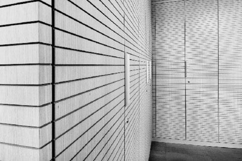 vista laterale di una parete bianca a righe nere con vicino una porta e di fronte un mobile