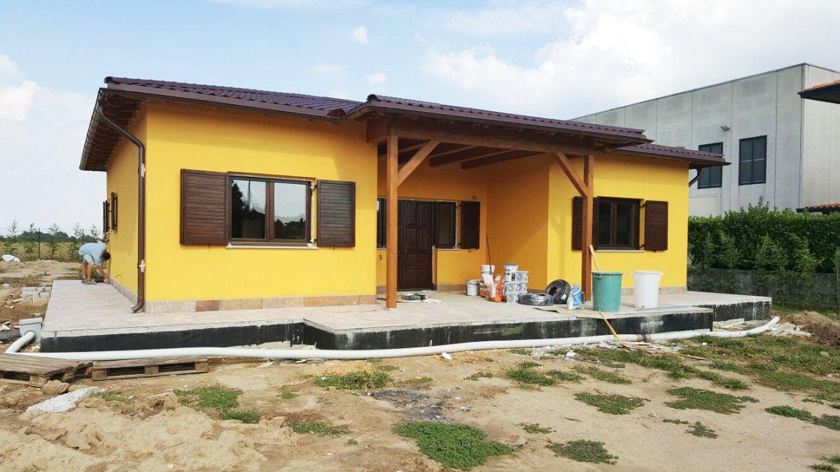 una casa gialla con  persiane in legno