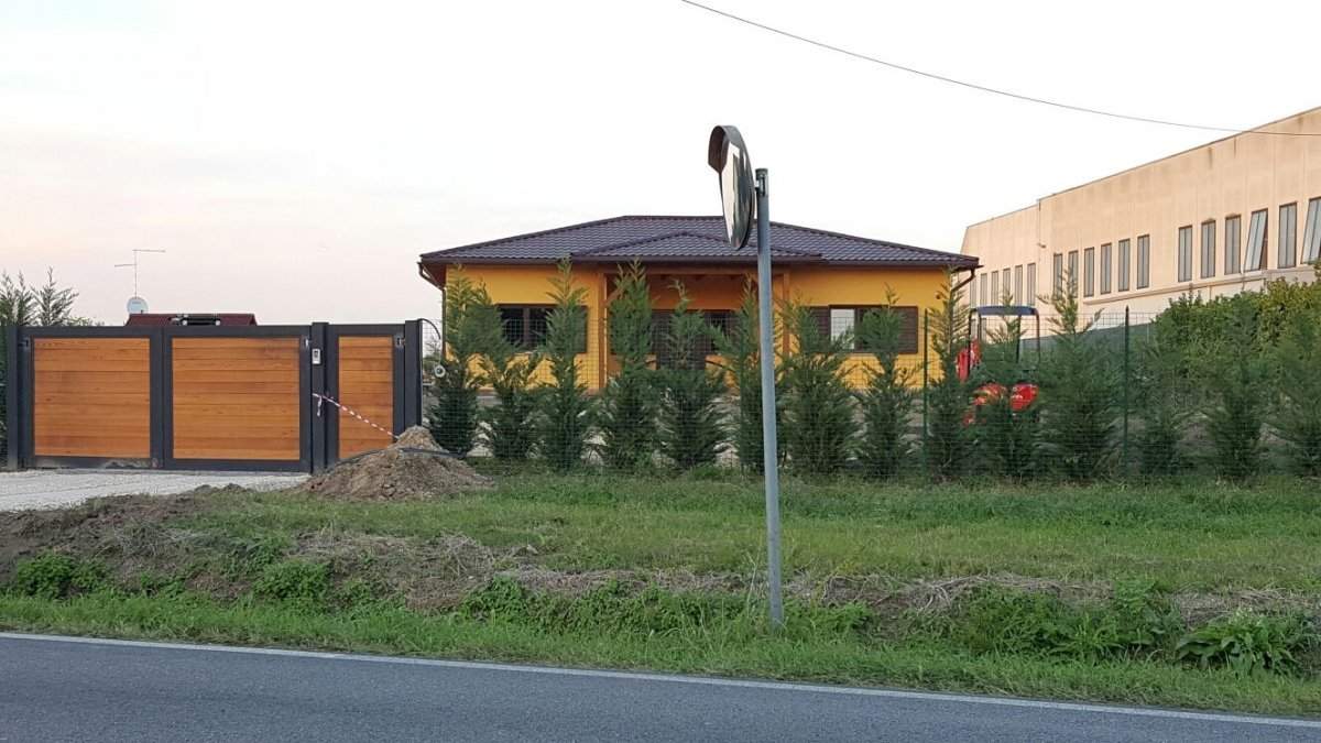 vista di un prato in lontananza di una casa gialla