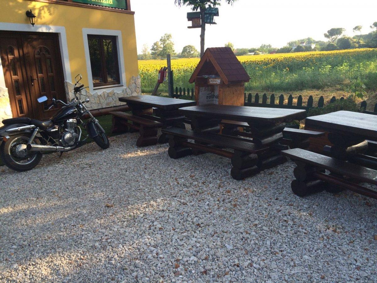 dei tavoli e delle panche in legno scuro e una moto