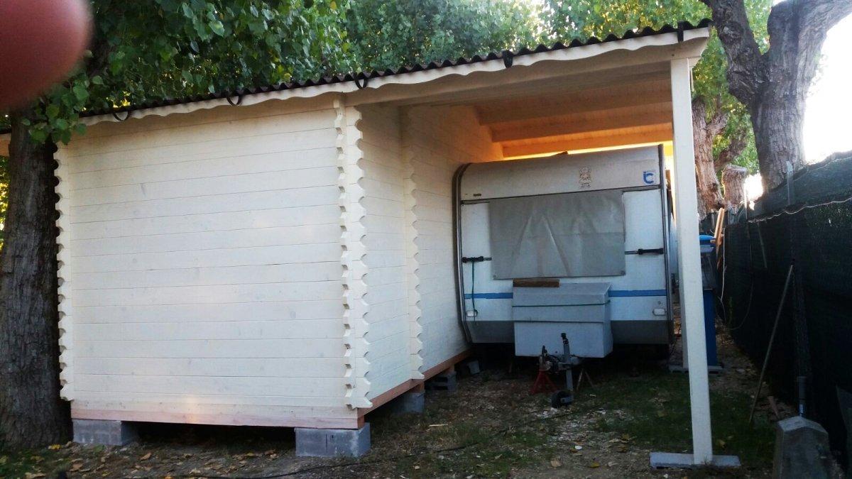 una roulotteuna casetta in legno con una roulotte parcheggiata