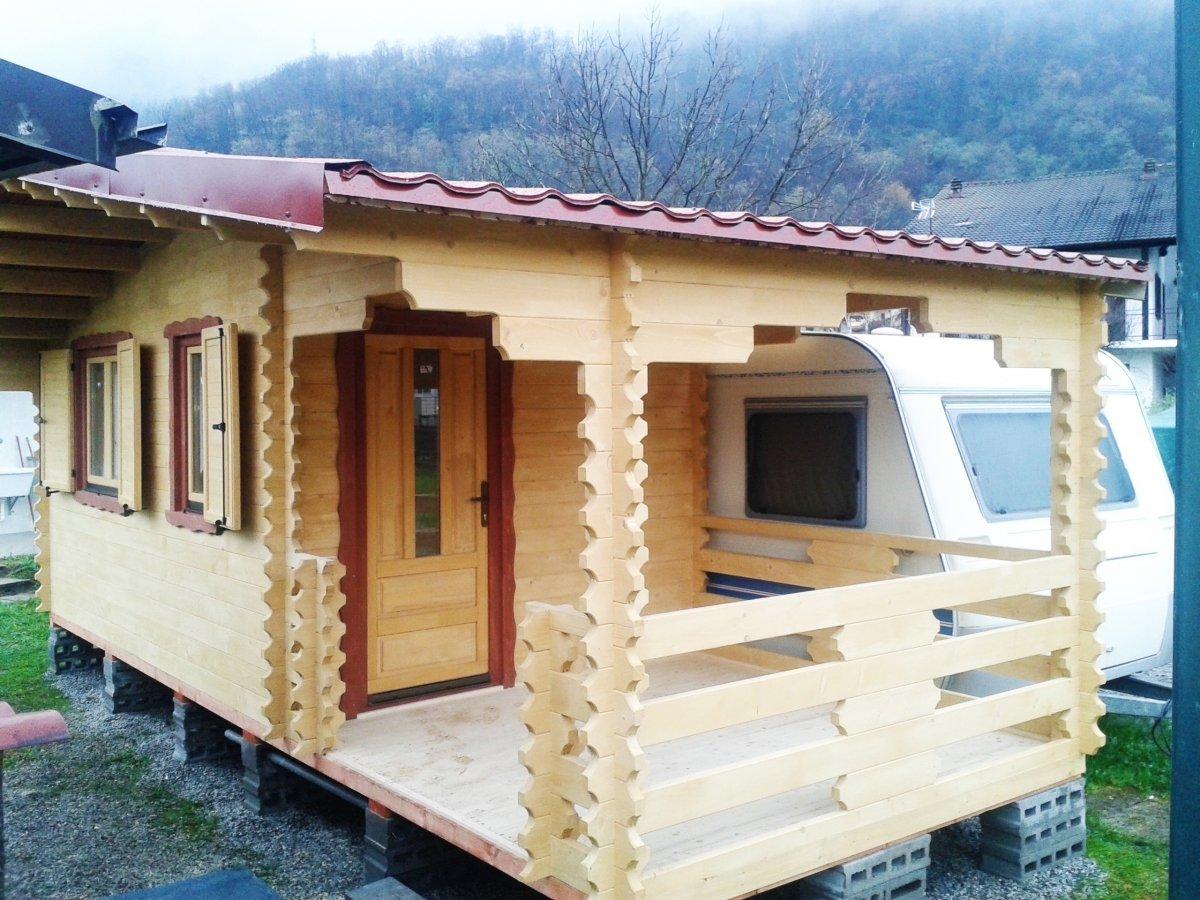 una casetta in legno e affianco una roulotte