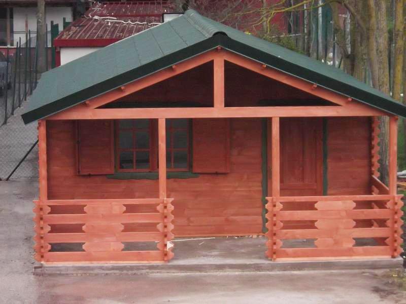 una casetta in legno con un tetto verde