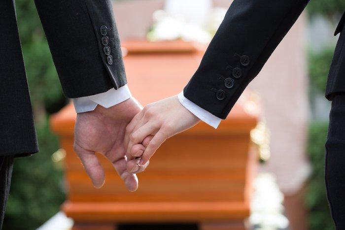 due persone si tengono per mano davanti a una bara