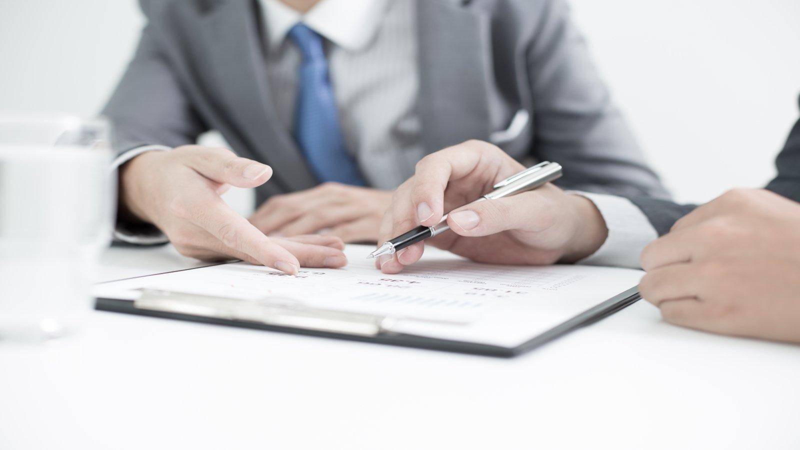 Le mani di due uomini che parlano su documenti e che uno segnala con il biro