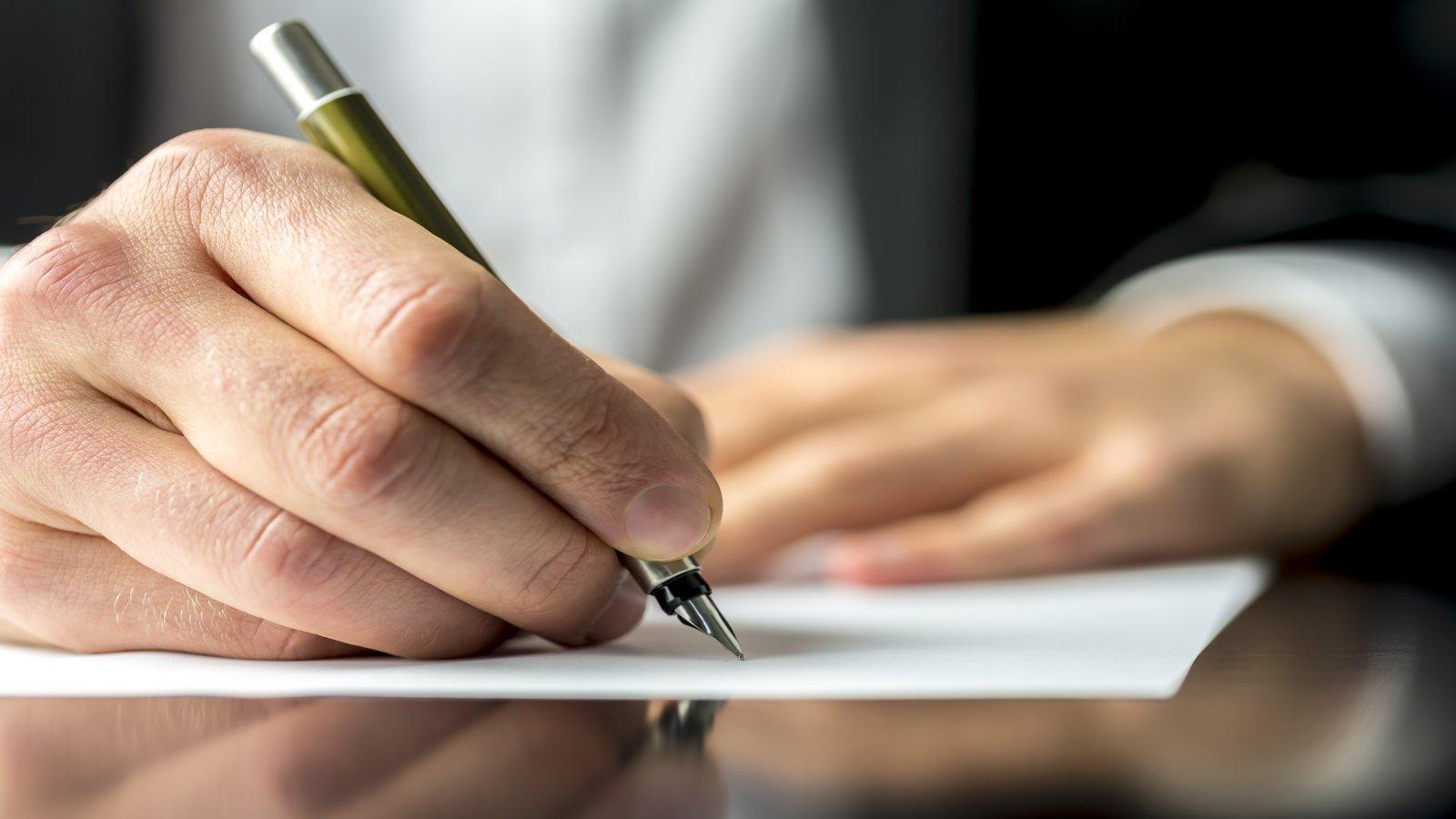 La mano di un uomo scrivendo con una penna