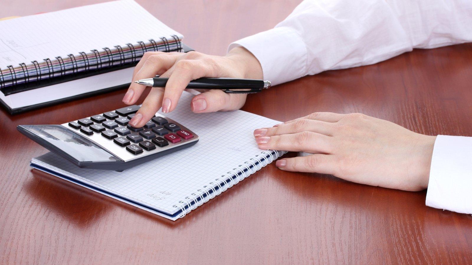 La mano di una donna che soggetta un biro usando una calcolatrice accanto a un quaderno