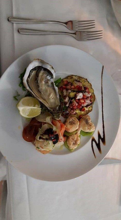 un piatto con ostriche,gamberi,melograno e verdure